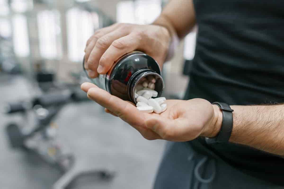 bcaa tablets na palma da mão de um atleta