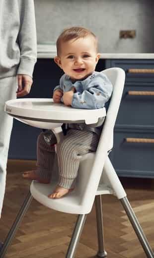 um bebê sentado na cadeira de alimentação