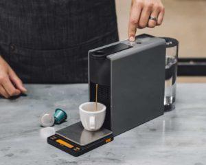 fazendo café com uma cafeteira nespresso premium em cozinha