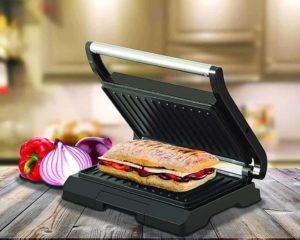 sanduicheira oster na mesa com sanduíches a carnes