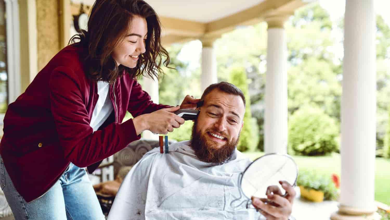 mulher cortando cabelo de esposo
