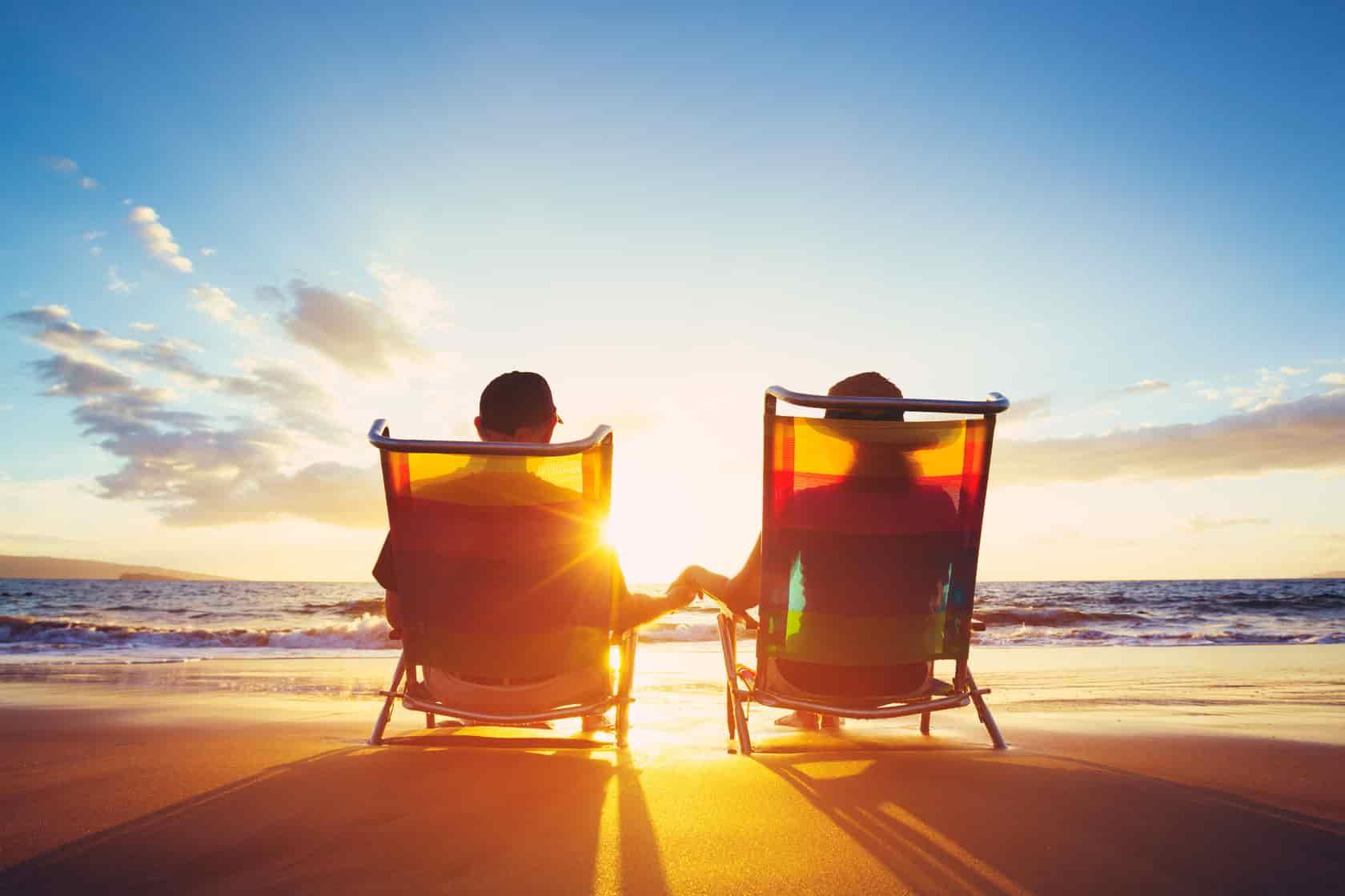 duas pessoas sentadas nas cadeiras de praia durante pôr de sol