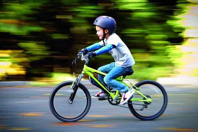 menino andando de bicicleta com capacete infantil