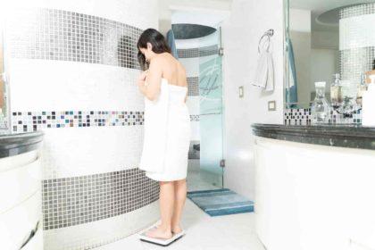 mulher pesa na balança digital corporal depois de banho