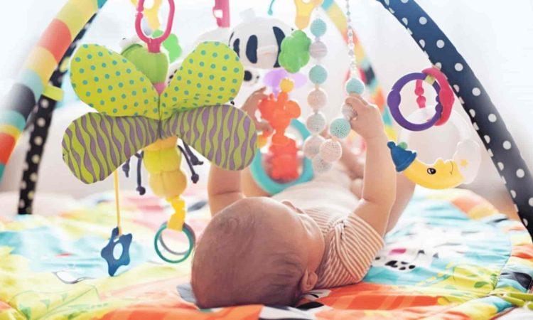 um bebê brincando no tapete de atividade educativo
