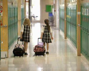 duas meninas usando mochila de rodinha na escola